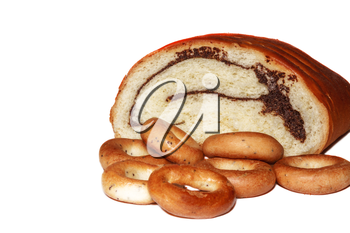 Broken roll with poppy seeds and bagels on white background