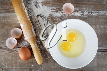 Cooking still life with eggs, eggshells, flour and rolling pin.
