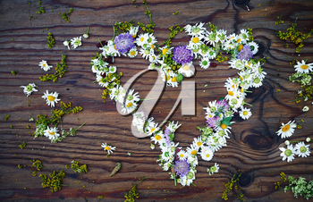 Heart symbol made of flowers on vintage wooden table background. Top view.