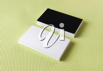 Several black and white business cards on a green background.