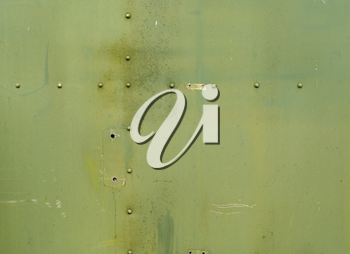 Abstract painted matte green metal background texture with rivets. Riveted  military green metal.