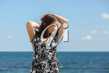 Young long-haired woman posing on a background of blue sky and sea on a clear sunny day. Blurred background. Focus on model.
