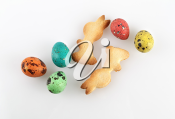 Colored quail eggs and biscuits in the shape of rabbits.