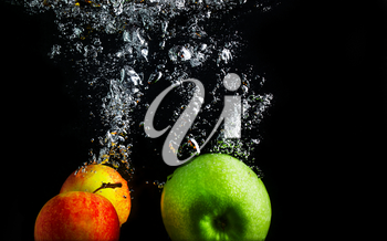 Apples falling into the water with a splash and air bubbles. Healthy food on black background. Wash fruits.