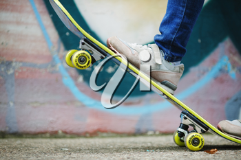 Skateboard stunt training. Skateboard and children's feet in sneakers against wall background. Healthy lifestyle concept. Shallow depth of field. Selective focus.