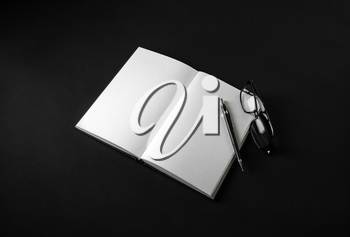 Blank open book, pencil and glasses on black background. Responsive design mockup.