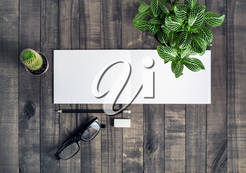 Blank stationery template. Notebook, pencil, eraser, glasses and plants on wooden background. Flat lay