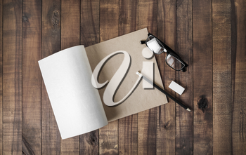 Blank notepad and stationery: glasses, pencil and eraser on wooden background. Flat lay.