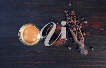 Coffee espresso cup, roasted coffee beans and ground powder on vintage wooden background. Top view. Flat lay.