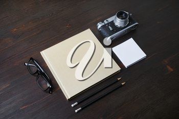 Blank stationery and retro camera on wood table background.