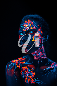 Conceptual face art with shining flowers painted in fluorescent colors isolated on black background