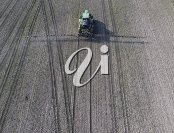 Tractor with hinged system of spraying pesticides. Fertilizing with a tractor, in the form of an aerosol, on the field of winter wheat