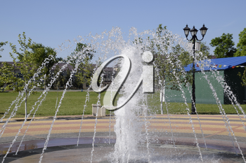 Splashes of a fountain in the park. Beautiful water jet emitted fountain.