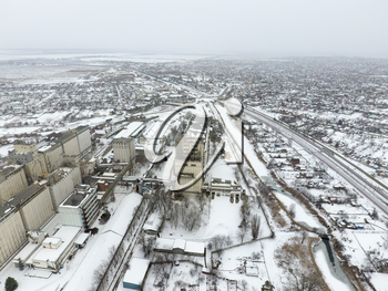 Sprinkled with snow grain elevator. Winter view of the old Soviet elevator. Winter view from the bird's eye view of the village. The streets are covered with snow.
