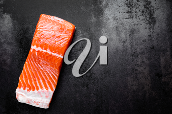 Raw salmon or trout sea fish fillet on black metal background, top view