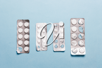 Pills blister pack on a blue background. The concept of disease treatment, healthcare
