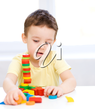 Cute little boy is playing with building blocks