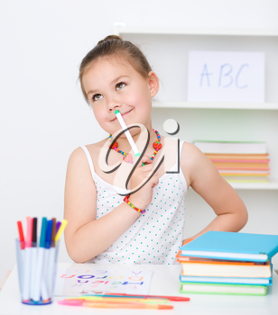 Cute girl is drawing using color pencils while sitting at table