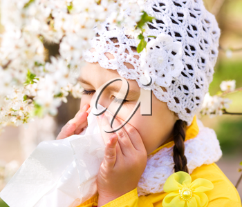Spring portrait of a little girl is blowing her nose
