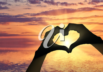 Love and feelings. Hands show a gesture of heart on the background of sea sunset