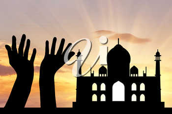 Concept of religion is Islam. Silhouette of hands facing the sky against a background of the evening mosque