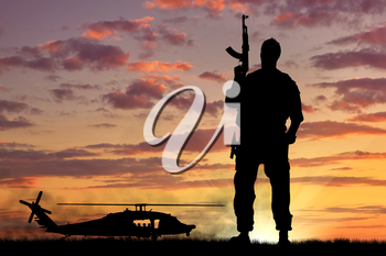 Silhouette of a soldier and helicopter at sunset