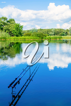 Concept of fishing and relaxation. Two fishing rods with a float on the background of beautiful scenery