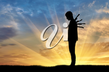 Betrayal and treachery concept. Silhouette of a sad man with a knives in the back on a sunset background