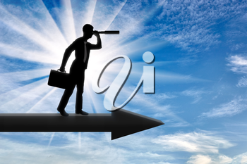 A silhouette of a businessman looking through a telescope into the distance while standing on the arrow. Business opportunity concept