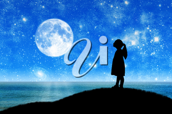 Silhouette, little girl child standing on a hill by the sea looking at the starry sky. Conceptual image of children's dreams