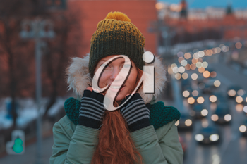 Beautiful winter portrait of young woman in the winter snowy scenery. Pretty red-haired girl walking on a winter evening city