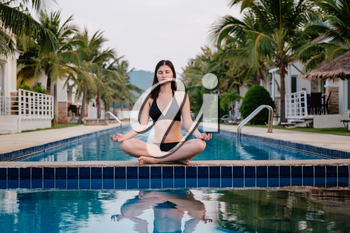 Vacation lifestyle scene of young woman sitting in swimming pool in morning time. Weekend and holiday lifestyle concept, morning meditation by the pool