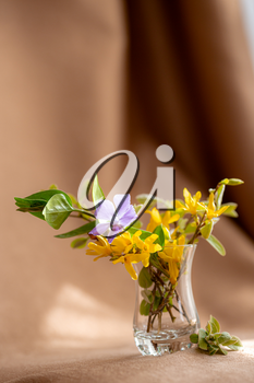 bouquet of yellow spring flowers in a glass vase in fabric background, warm shades. Vintage feminine styled photo.