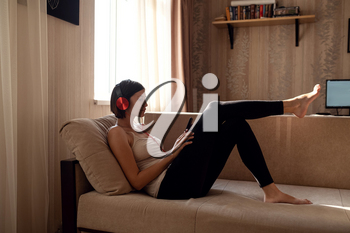 Young woman isolating at home and relaxing: stay at home social media campaign for coronavirus prevention. chatting with friends and using apps on a smartphone