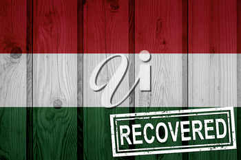 flag of Hungary that survived or recovered from the infections of corona virus epidemic or coronavirus. Grunge flag with stamp Recovered