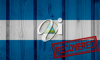 flag of Nicaragua that survived or recovered from the infections of corona virus epidemic or coronavirus. Grunge flag with stamp Recovered