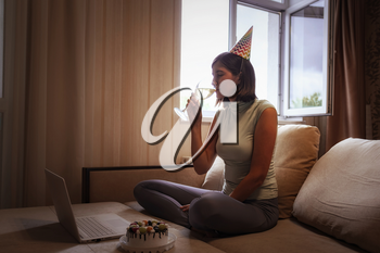 Girl celebrating birthday online in quarantine time. Woman celebrating her birthday through video call virtual party with friends. Authentic decorated home workplace. Coronavirus outbreak 2020.