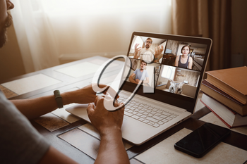 Back view of man talking to his colleagues about plan in video conference. Multiethnic business team using laptop for a online meeting in video call. Group of people smart working from home