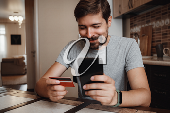hipster young man shopping online with credit card using smart phone at home. Indoor. online shopping concept.