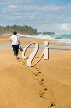 Senior caucasian woman walks down sandy Lumahai beach on Kauai Hawaii