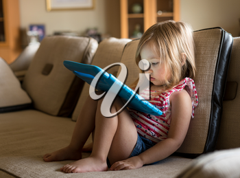 Young girl sitting at home on settee and using a child's tablet touch screen computer