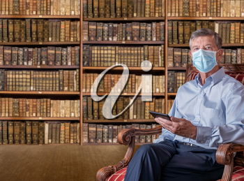 Senior caucasian man with a face mask against coronavirus reading an ebook tablet in old fashioned library of antique books