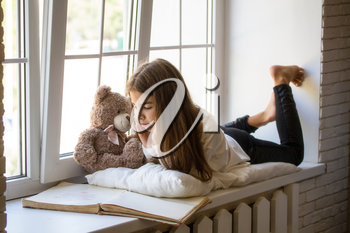 Little Girl lies on the windowsill next to her favorite toy bear cub and reads an old big book