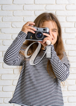 little girl in a striped blouse with a retro camera photographing standing near a light brick wall