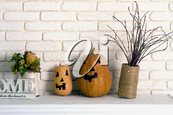 Two small pumpkins on a shelf decorated with child stand on a shelf