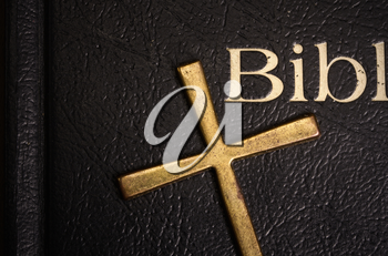 Holy Bible in a dark cover close-up and a metal brass cross lying on it