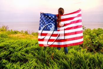 little American girl holding a star-striped US flagin her hands on the river bank