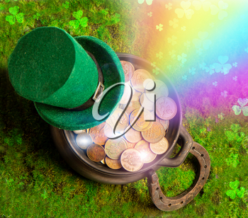 Leprechaun hat and horseshoe lie on green grass with rainbow and clover leaves and treasure pot