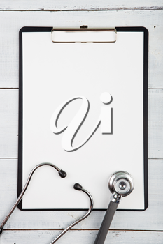 Workplace of doctor - stethoscope, medicine clipboard on wooden desk