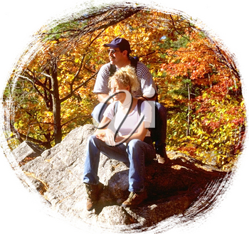 Royalty Free Photo of a Couple Sitting on a Rock in the Autumn Forest
